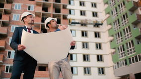 Foremans looking at the building plan. Two men are looking at the house and talking stock video