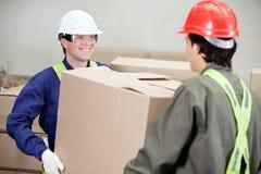 Foremen Carrying Cardboard Box At Warehouse. Two foremen carrying cardboard box at warehouse Royalty Free Stock Photo