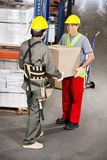 Foremen Carrying Cardboard Box At Warehouse Stock Photography