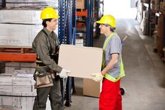 Foremen Carrying Cardboard Box At Warehouse. Two happy foremen carrying cardboard box at warehouse Stock Photography