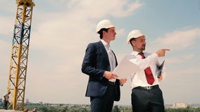 Foremen discuss problem at construction site stock footage