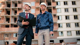 Foremen are discussing the building plan. Foremen are discussing the buildig plan. One of the men are smiling and talking with man in suit. The men are looking stock footage