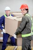 Foremen Lifting Cardboard Box in Warehouse. Portrait of two foremen lifting cardboard box in warehouse Royalty Free Stock Photography