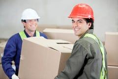 Foremen Lifting Cardboard Box At Warehouse. Two foremen lifting cardboard box at warehouse Royalty Free Stock Image