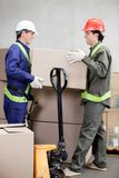 Foremen Lifting Cardboard Box At Warehouse. Two foremen lifting cardboard box at warehouse Stock Images