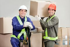 Foremen Loading Cardboard Boxes At Warehouse. Two happy foremen loading cardboard boxes at warehouse Royalty Free Stock Photo