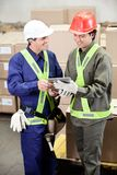 Foremen Using Digital Tablet in Warehouse. Happy young foremen using digital tablet in warehouse Stock Images