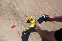 Forensic hand use mobile phone take picture of evidence with evi. Law enforcement or forensic take picture of evidence from car bomb with marker and ruler by Royalty Free Stock Photo
