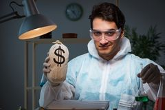 The forensic investigator working in lab looking for evidence. Forensic investigator working in lab looking for evidence royalty free stock photography