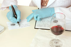 Forensic Science obtaining fingerprints. A crime scene forensic scientist obtains fingerprints from a glass using latent powder and tape and then writes down Royalty Free Stock Images