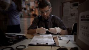 Forensic scientist male examining the evidence bullet from the crime scene royalty free stock images