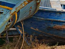 Abandoned boats. In a Sicilian port, the plating of these wrecks is ruined . Graphic colored  drawings can still be seen in the foresections Royalty Free Stock Photos