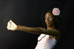 Foresighting. Portrait of beautiful african-american woman in pink dress and pink camellia in the hair Royalty Free Stock Photography