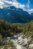 Forest in Argentière with glacier creek, village and snowy mountains. In the background, blue sky with clouds, French Alps Royalty Free Stock Images