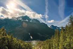 Forest in Argentière with snowy mountains and village. In the background, blue sky with clouds, French Alps Royalty Free Stock Image