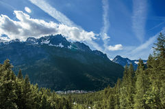 Forest in Argentière with snowy mountains and village. In the background, blue sky with clouds, French Alps Royalty Free Stock Photography