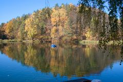 Forest in autumn with boat, reflection royalty free stock image