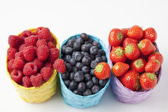 Forest berries, raspberries, blueberries and strawberries in baskets. Studio shot, on white background Stock Photo