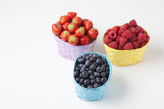 Forest berries, raspberries, blueberries and strawberries in baskets. On white background Stock Images