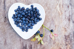 Forest blueberries heart plate wooden background Stock Photo