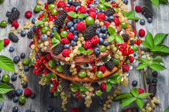 Forest cake made of fresh wild fruit. On old wooden table stock photos