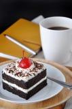 Forest Cake negro con el cuaderno y el café en fondo Fotografía de archivo libre de regalías
