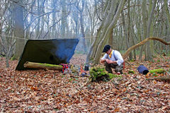 Forest camp man in woods. Photo of a man in beret around campfire and preparing traditional south american yerba mate from gourd and bombilla in the woods around Stock Photo