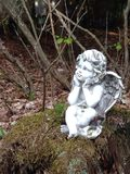 Forest cherub. Statue of angel in the woods weathered Stock Image