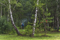 In the forest in the clearing the man leaned over the barbecue Royalty Free Stock Images
