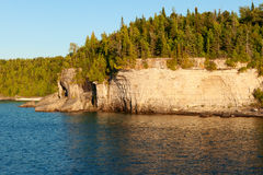 Forest and Cliffs at Lakeshore Stock Photography