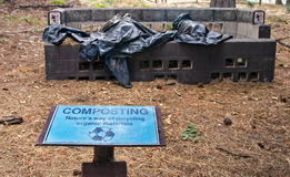 Forest Compost Bin. Compost bin in forest area with blue sign in foreground and pine needles on the ground Stock Photography