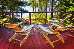 Forest cottage deck and chairs. Wooden deck of cottage with Adirondack chairs at lake Royalty Free Stock Photography