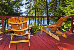 Forest cottage deck and chairs. Wooden deck at forest cottage with Adirondack chairs Royalty Free Stock Images