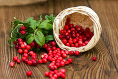 Forest cranberry lying on a wooden table Royalty Free Stock Photography