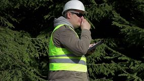 Forest engineer with tablet PC near fir stock footage
