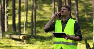 Forest evaluation and management - forestry engineer working with digital tablet in the woods