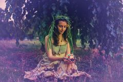 Forest fairy holds lamp with a candle. Forest fairy, in a wreath of willow branches, sits on a meadow under a mulberry tree,  carefully holds a lamp with a Stock Photo