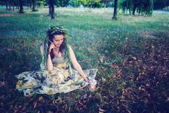 Forest fairy sits on a meadow Royalty Free Stock Photo