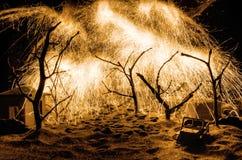 Forest Fire brinnande träd för löpeld i röd och orange färg på natten På tabellgarnering med fyrverkeriträdfilialer och sand royaltyfri fotografi