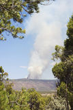 Forest Fire or Controlled Burn atop Mesa. Far in the distance, atop a mesa in the desert, a fire burns. It could be a forest fire or a controlled burn royalty free stock photo