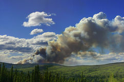 Forest Fire in Hills in Interior Alaska. A forest fire creates am huge plume of smoke as it blazes through forests over the hills Royalty Free Stock Photography