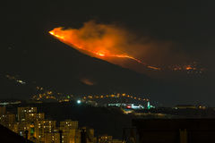 Forest fire in the mountains above the city, flames next to hous Stock Image