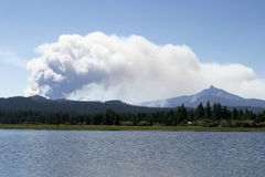 Forest Fire Smoke Close. A cloud of smoke rises from the Lake George forest fire in Central Oregon in 2006. The plume of smoke is rising over Mt. Washington in stock photography