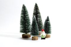 Forest firs and garden gnome. Isolated group of full artificial firs like a small forest tree with a figurine of garden gnome inside on a white background Stock Photo