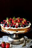 Forest fruits cake. Layer cake with forest fruits and whipped cream on a vintage dark background Stock Image