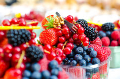Forest fruits like a blueberries, raspberries, strawberries, red currants on a market. On a white tablecloth. Harvesting, agricult Stock Photo
