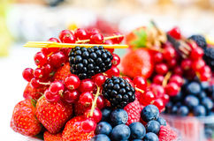 Forest fruits like a blueberries, raspberries, strawberries, red currants on a market. On a white tablecloth. Harvesting, agricult Stock Images