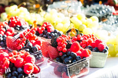 Forest fruits like a blueberries, raspberries, strawberries, red currants on a market. On a white tablecloth. Harvesting, agricult Royalty Free Stock Images
