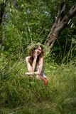 FOREST GIRL. Beautiful young woman sitting on the grass in a forest. Girl with flower chaplet Stock Photo