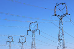 Forest of high voltage towers under blue sky Stock Images